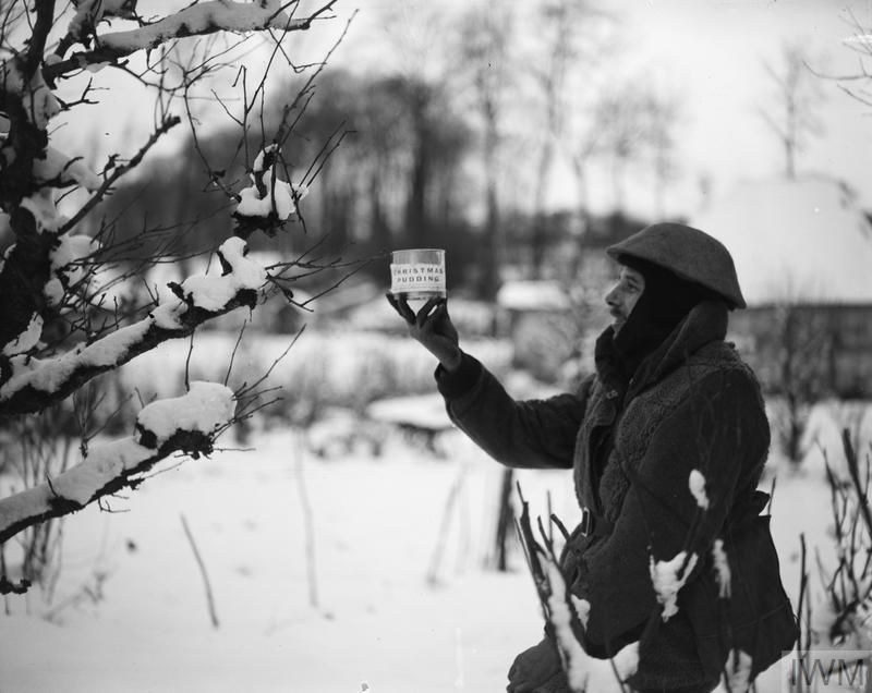 British soldier (Army Service Corps?) displaying a can of Christmas pudding at snow-covered Neulette, 17 December 1917.