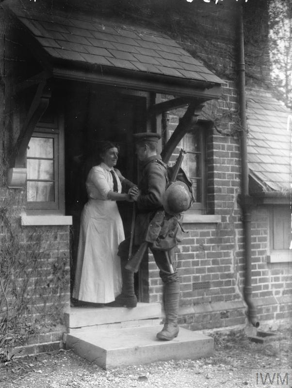 "A soldier of the Sherwood Foresters (Nottinghamshire and Derbyshire Regiment) is greeted on the door step by his mother as he arrives home on leave, laden with kit. This photograph is part of a sequence of posed photographs entitled ""Fourteen Days' Leave"" which follow this soldier's reunion with his mother."