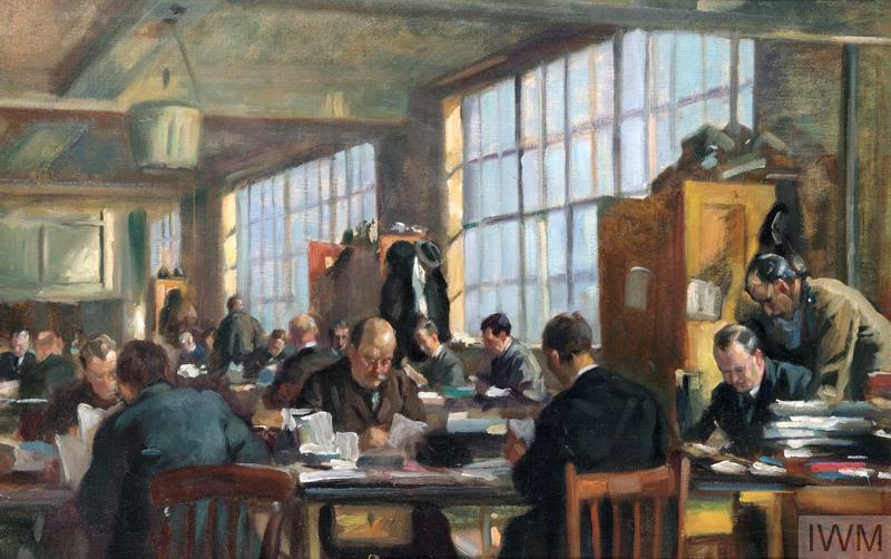 The interior of a room with large windows, within which numerous men are working at long tables covered with paperwork. On the right an officer in military uniform stands beside a seated man wearing a suit, both of them looking down at paperwork on the table. All of the other men wear civilian suits.