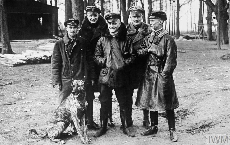 Smiling Manfred von Richthofen, the Commander of Jasta 11, surrounded by his fellow pilots and his dog Moritz, at Roucourt, France. Left to right: Vizefeldwebel Sebastian Festner (nine victories that month, killed on 23 April), Leutnant Karl-Emil Schäffer (fourteen victories), Oberleutnant Manfred von Richthofen (22 victories), his brother Leutnant Lothar von Richthofen (fourteen victories) and Leutnant Kurt Wolff (21 victories).