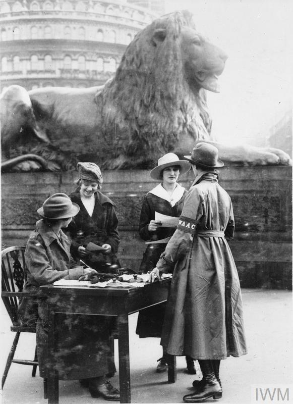 A Women's Auxiliary Army Corps recruiting sergeant and assistant talking to potential recruits in Trafalgar Square in London, 1918.