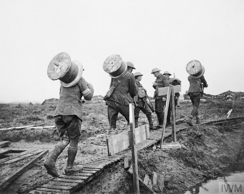 Battle of Poelcappelle. Royal Engineers taking drums of telephone wire along a duckboard path up to the front between Pilckem and Langemarck, 10 October 1917.