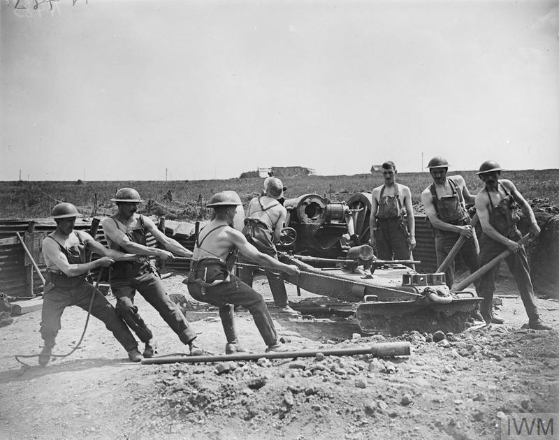 Crew of the 6-inch 26cwt howitzer battery of the Royal Garrison Artillery, stripped to the waist, moving the howitzer on to a new target. Near Achicourt, 27 May 1918. © IWM (Q 11026)