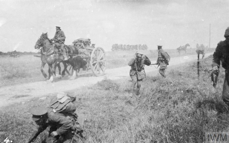 Troops of the 1st Battalion, Middlesex Regiment (Duke of Cambridge's Own) under shrapnel fire from German artillery on the Signy-Signets road, 8 September 1914. The man with the goggles belongs to the Intelligence Corps. He is badly wounded in the head and his face is covere with blood.
