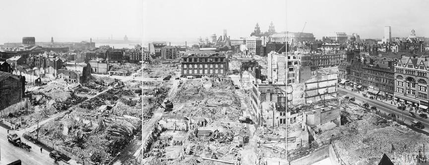 A panoramic view of the city of Liverpool, showing bomb damage received after an air raid. The Liver Building can be clearly seen just to the right of centre, and the River Mersey is just visible to the left of the photograph.