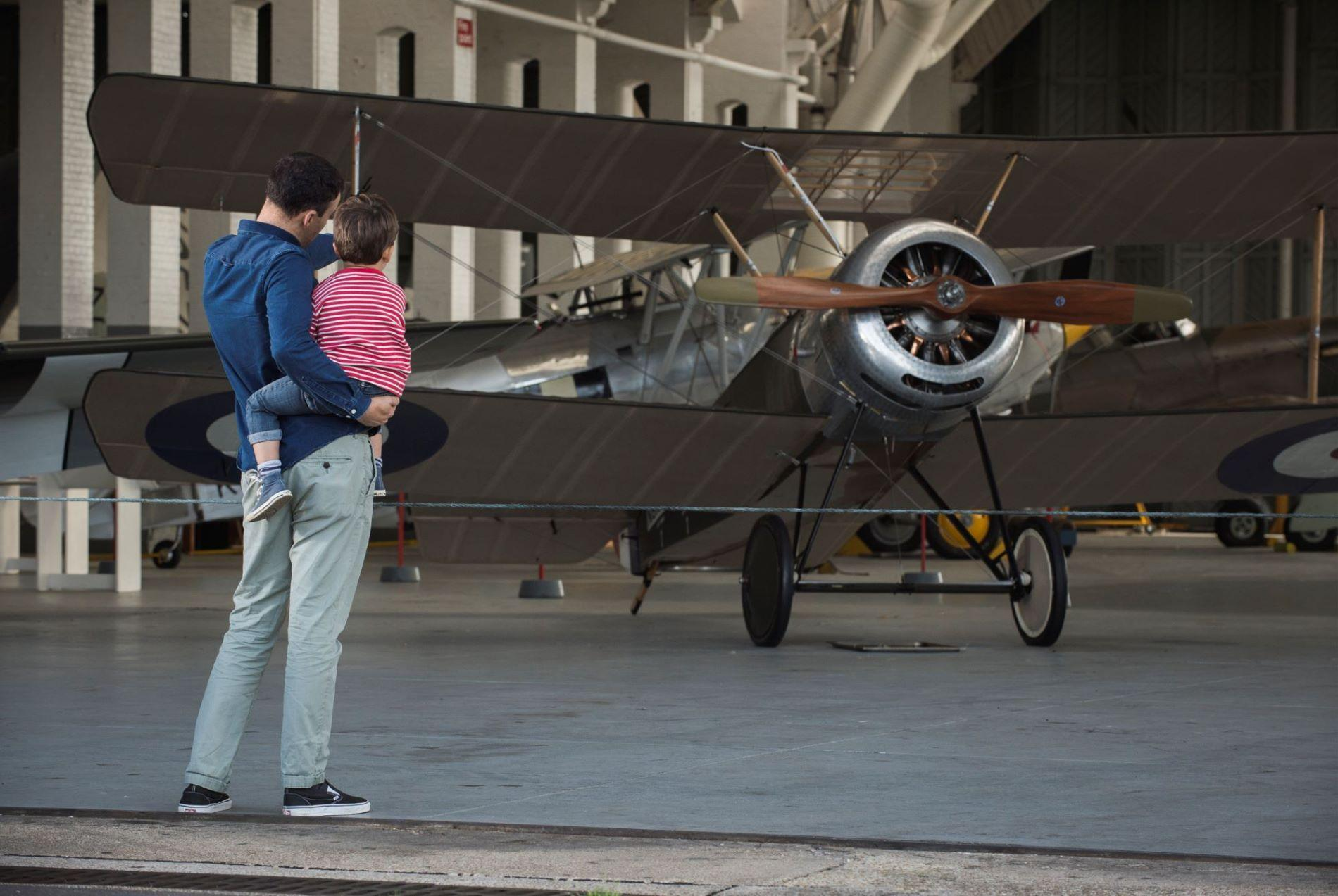 A father holds a young child standing in front of a biplane at IWM Duxford