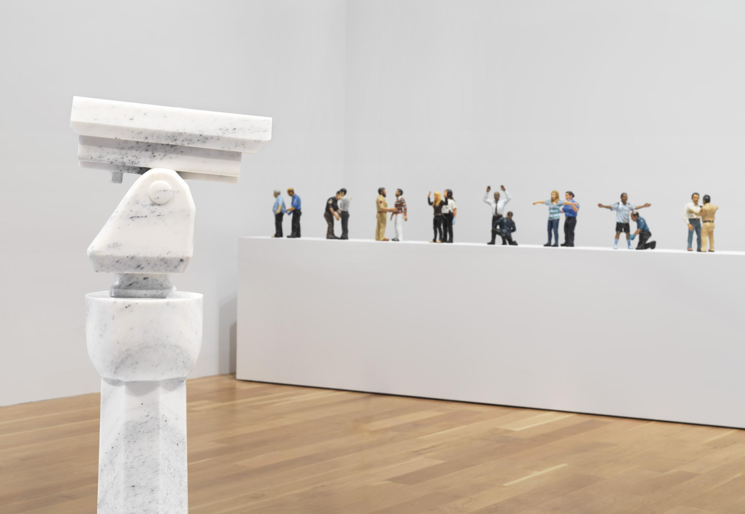 View of gallery showing marble surveillance stand and figures
