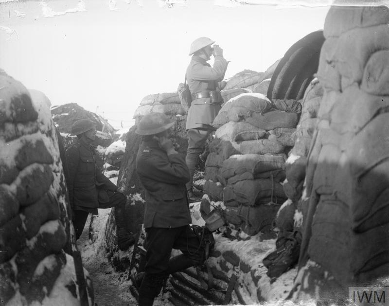 A Royal Artillery FOO (Forward Observation Officer) observing from the fire step of a trench near Croisilles, 4 January 1918