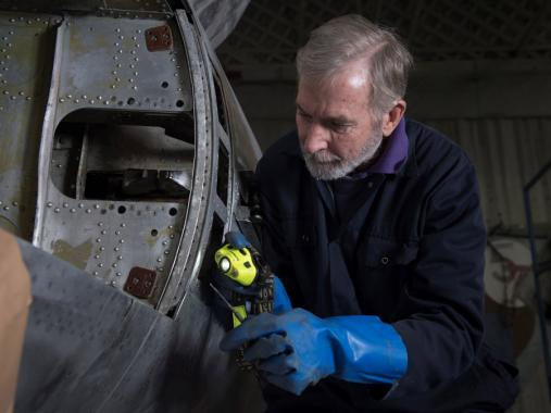 A volunteer at work as part of the Hangar 5 conservation team at IWM Duxford