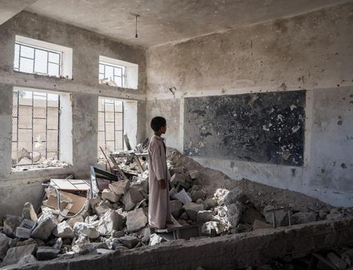 A student from Aal Okab school stands in the ruins of his classroom. The school was on the outskirts of Saada, in the north of Yemen, and was heavily bombed in 2015 after Houthi fighters were reported to have taken refuge in the buildings.
