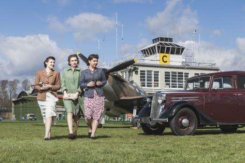 Actresses in 1940s dress pose with car at IWM Duxford