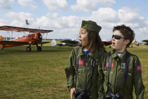 Girl and Boy in flying suits are excited by aircraft at Duxford Air Festival
