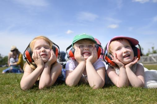 3 girls facing the camera laying on the grass at Duxford Air Festival