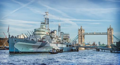 HMS Belfast with Tower Bridge behind with a bright blue sky. Imperial War Museums venue hire.