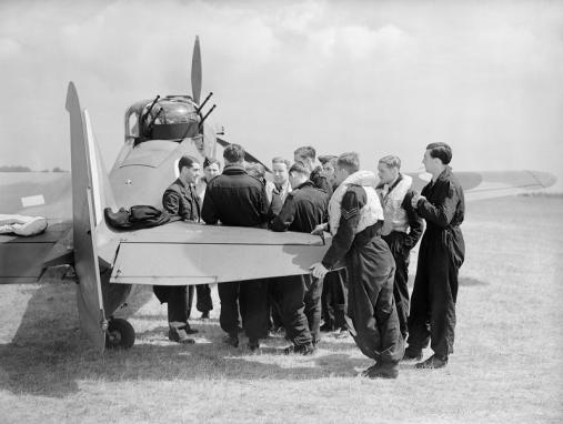Squadron Leader P A Hunter (far left), the CO of No. 264 Squadron RAF, briefs his pilots by one of the Squadron's Boulton-Paul Defiants at Duxford, 31 May 1940.
