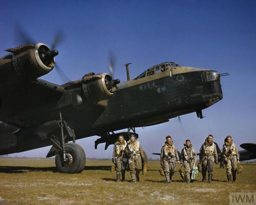 Colour photograph of an aircrew in full flying kit walking beneath the nose of Short Stirling Mark I