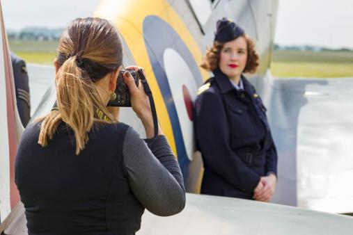 A model dressed in Second World War uniform poses next to a Spitfire being photographed