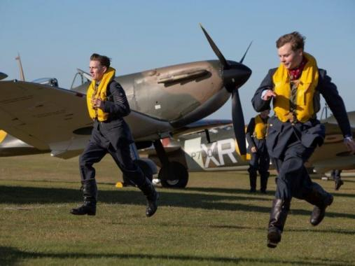 Two reenactors dressed as Battle of Britain pilots scramble at IWM Duxford