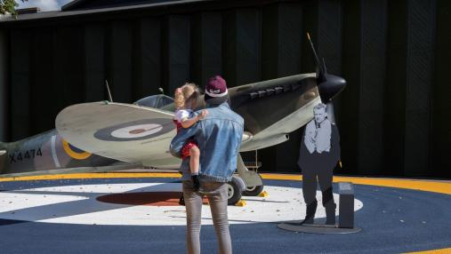 Father and daughter in front of a Spitfire at IWM Duxford's Battle of Britain exhibition