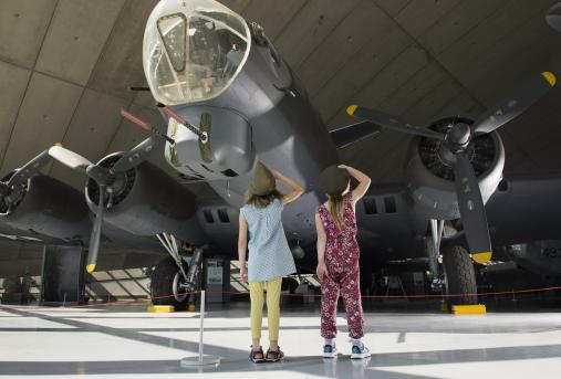 A pair of children look up at the nose of the B-17 in the American Air Museum
