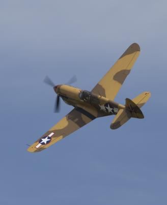 P-40 in Flight against a blue sky at Flying Legends