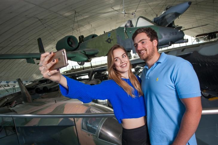 Couple taking a phone selfie in the American Air Museum