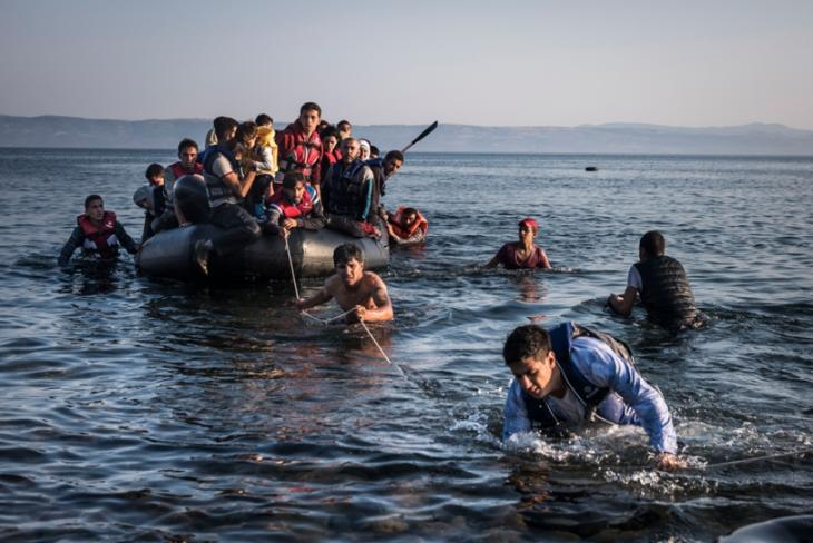 This image from The Exodus shows an inflatable dinghy, crowded with refugees and migrants, as it is pulled ashore on the island of Lesbos.