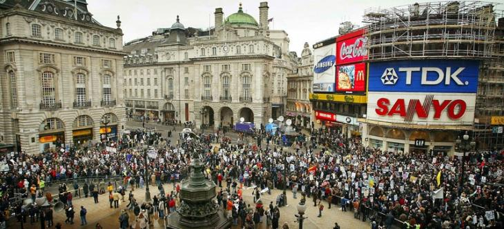 Protesters march through Piccadilly Circus in London, 15 February 2003. After assembling at different points, the two mass groups of protesters converged at Piccadilly Circus.