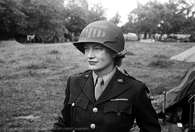 Lee Miller in steel helmet specially designed for using a camera, Normandy, France 1944 by unknown photographer. Photographer Unknown © The Penrose Collection, England 2015. All rights reserved.