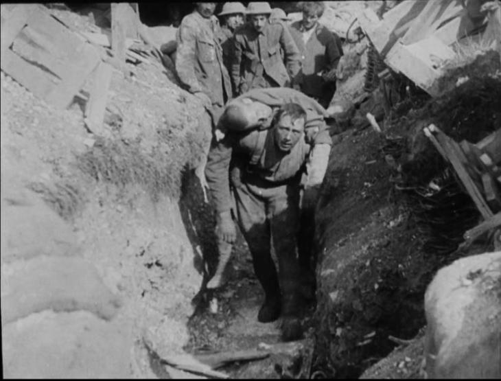 The famous still taken from The Battle of the Somme showing a soldier in a trench carrying a wounded man on his back.