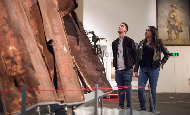 Visitors at IWM North viewing a piece of twisted steel retrieved from the rubble of the World Trade Center on display in the Main Exhibition Space.