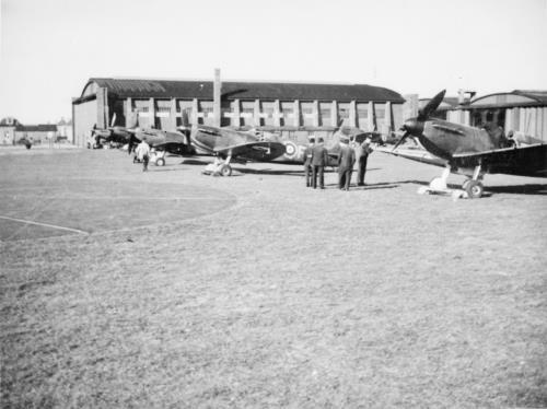 Archive photo of RAF Duxford depicting planes on the ground in front of a hanger