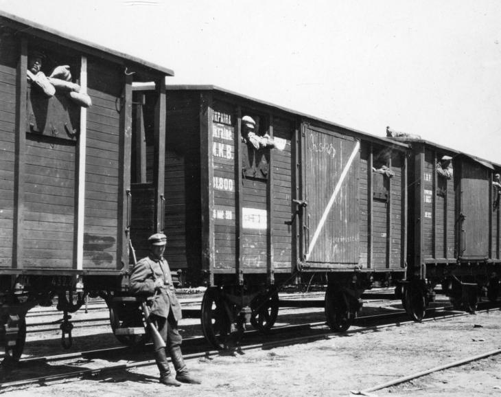 Polish soldier guarding a train, loaded with Soviet prisoners.