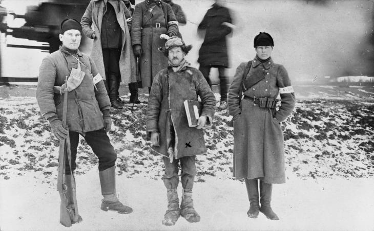 Three men standing - Estonian Bolshevik Commissar (middle) captured by soldiers of the Estonian National Army near Palupera, Tartu county.