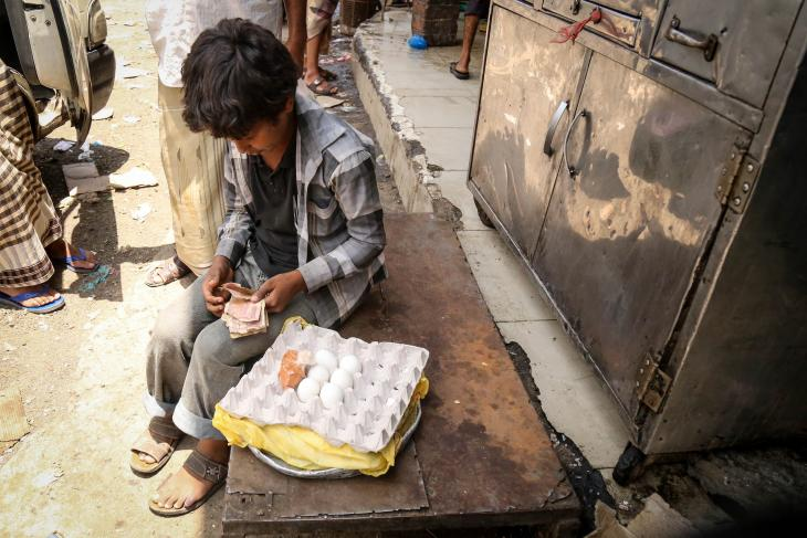 A child, impoverished due to the ongoing war in Yemen, counts his money he has made from selling boiled eggs. Yemen, Taiz City, Jamal Street, 3 September 2017. Photograph Ahmed Basha