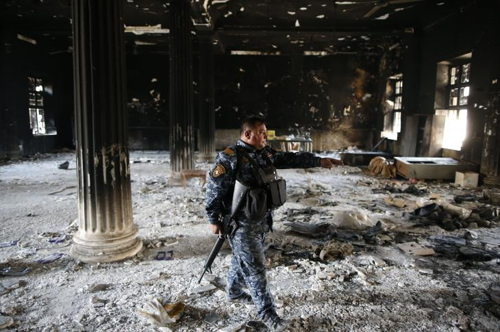 A member of the Iraqi forces inspects the damage inside the destroyed museum of Mosul on April 2 2017 after they recaptured it from Islamic State (IS) group fighters. Photograph AHMAD GHARABLI/AFP/Getty Images.