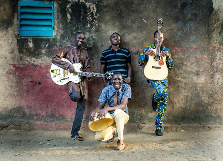 The four members of Songhoy Blues holding their instruments.