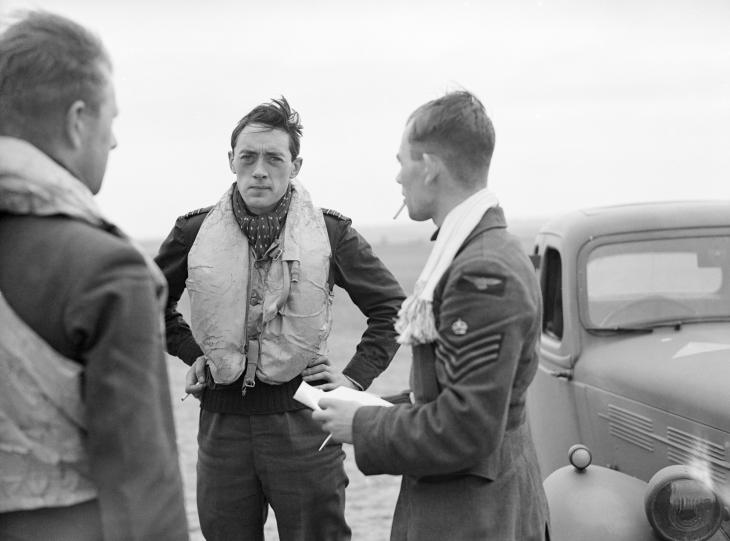 Three pilots of No. 19 Squadron RAF confer at Fowlmere, Cambridgeshire, after a sortie.