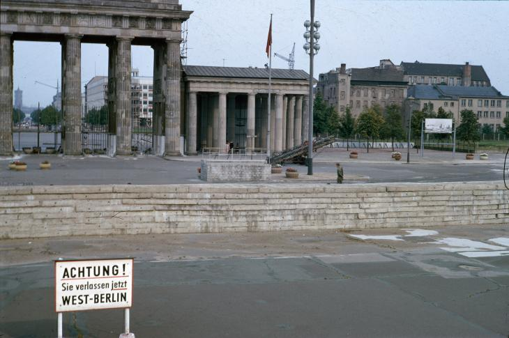 View of the wall as seen from the American sector, looking towards the Brandenburg Gate, where an East German guard patrols in the background.