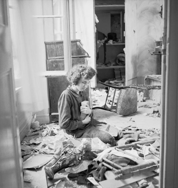 Mari-Anne Le Du clasps a treasured book in the ruins of her house in the village of Buron, Normandy, July 1944.