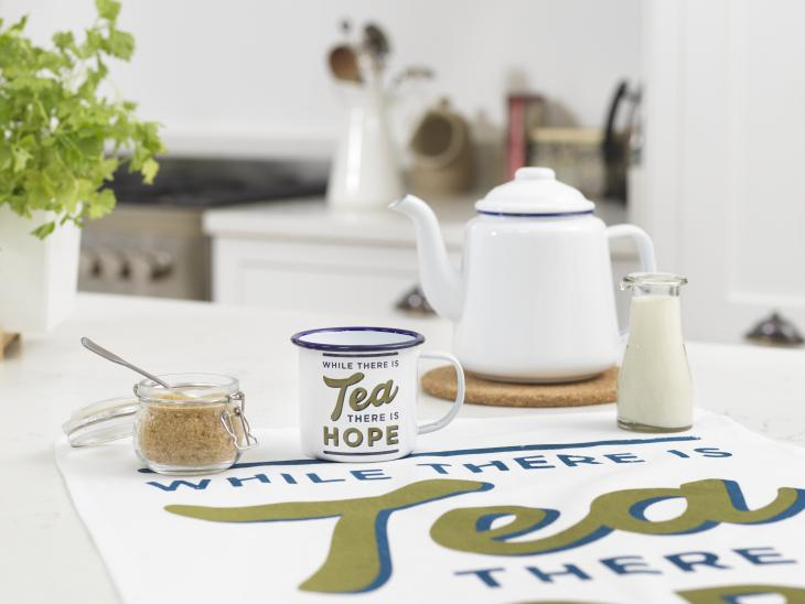 A collection of homeware available from the IWM shop including a mug that reads 'while there is tea there is hope'