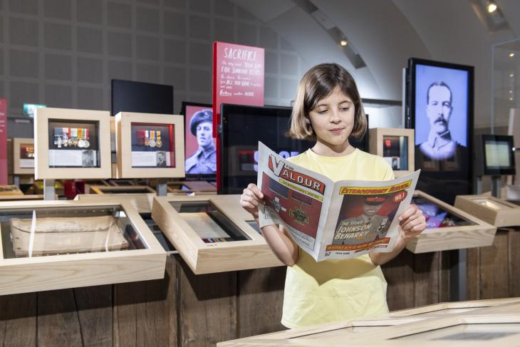 Girl reads a comic book in the gallery