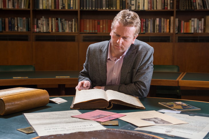 An IWM curator examines a book from the collection