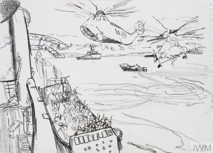 A view from the deck of a large ship, looking down over landing craft below filled with troops. Two helicopters circle above, and in the background are another large ship and landing craft.
